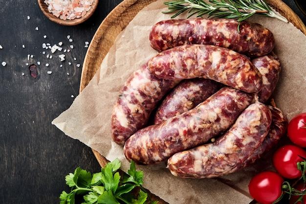 Salsichas crus ou bratwurst em papel manteiga e ingredientes para cozinhar. vista superior com espaço de cópia na mesa de pedra.