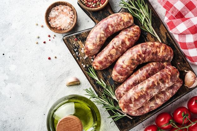 Salsichas crus ou bratwurst na tábua de cortar com especiarias e ingredientes para cozinhar. vista superior com espaço de cópia na mesa de pedra cinza claro.