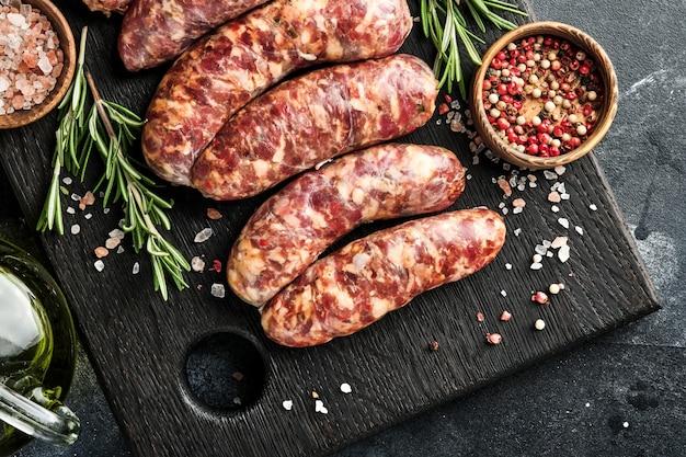 Salsichas crus ou bratwurst na tábua de cortar com especiarias e ingredientes para cozinhar. vista superior com espaço de cópia na mesa de pedra.