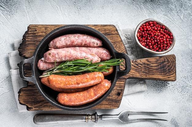 Salsichas crus sortidas chorizo e bratwurst com especiarias em uma panela com alecrim