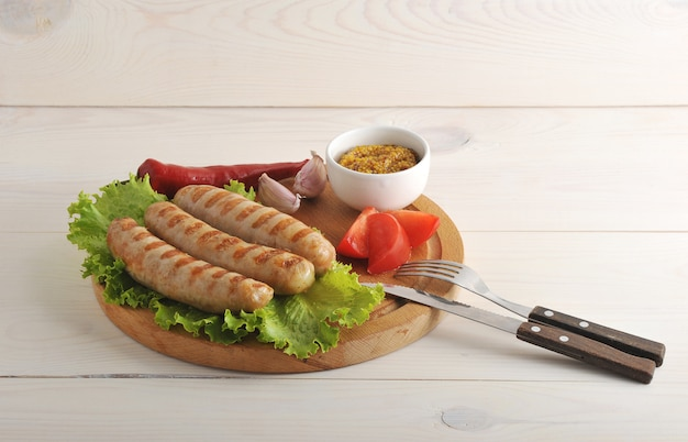 Salsichas da baviera grelhadas em uma tábua de madeira redonda