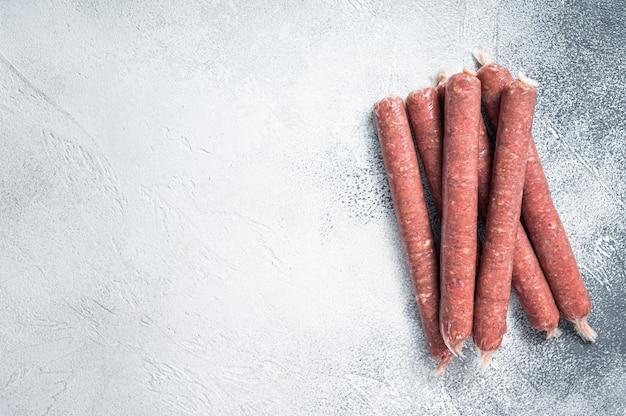 Salsichas de açougueiro cru com peles com ervas na mesa da cozinha. fundo branco. vista do topo. copie o espaço.