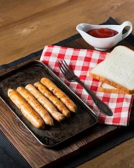 Salsichas de ângulo alto na bandeja com pão