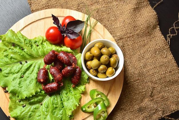 Salsichas de caça em uma placa de madeira com alface, manjericão, tomate cereja, pimentão e azeitonas.