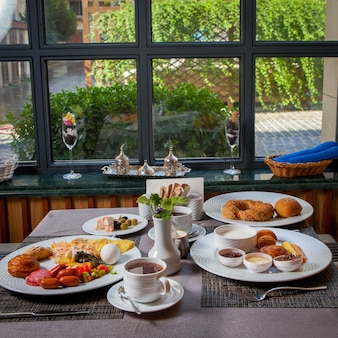 Salsichas de café da manhã, ovo cozido, omelete, croissant em pratos e xícara de chá na mesa