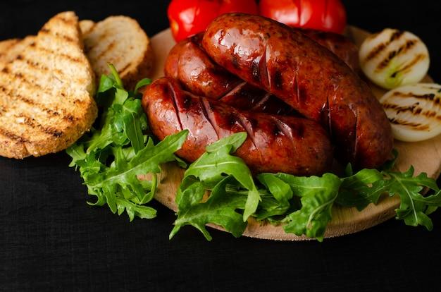 Salsichas de carne de porco grelhadas com rúcula e vegetais no fundo preto. .