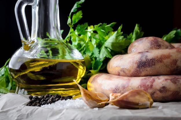 Salsichas de carne, especiarias e azeite de oliva em um fundo escuro