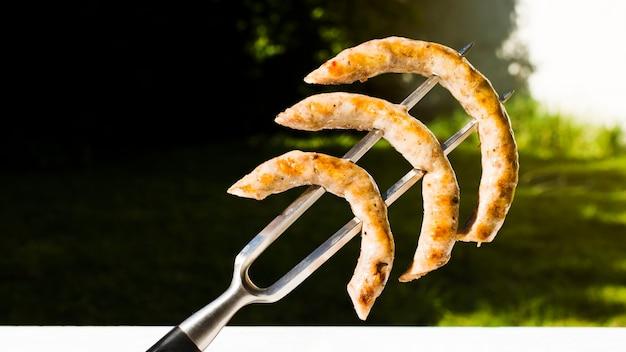 Salsichas de churrasco amarradas no garfo