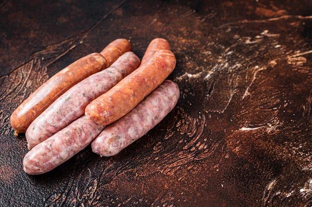 Salsichas de churrasco cruas chouriço e bratwurst com especiarias. fundo escuro. vista do topo. copie o espaço.