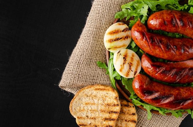 Salsichas de churrasco, torradas de pão, cebola e rúcula fresca em fundo preto. configuração plana