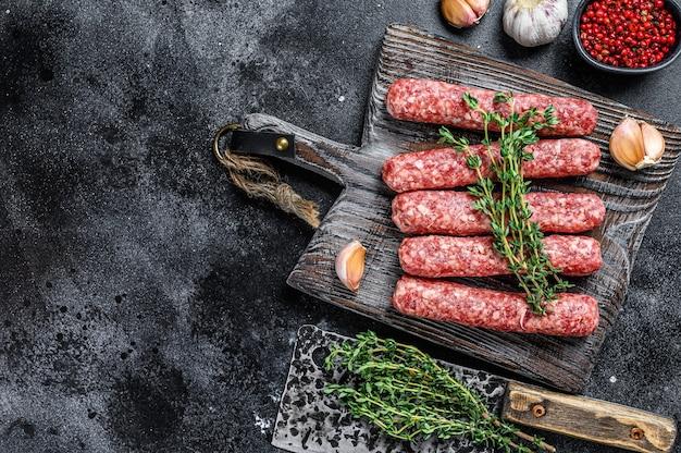 Salsichas de espetinhos de carne crua fresca em uma tábua