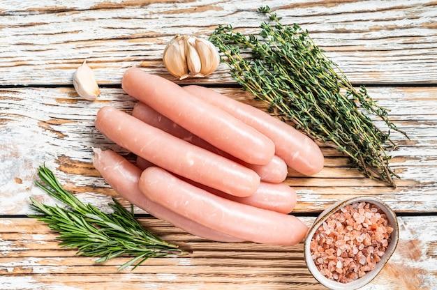 Salsichas de frango cru em uma mesa de cozinha de madeira com ervas