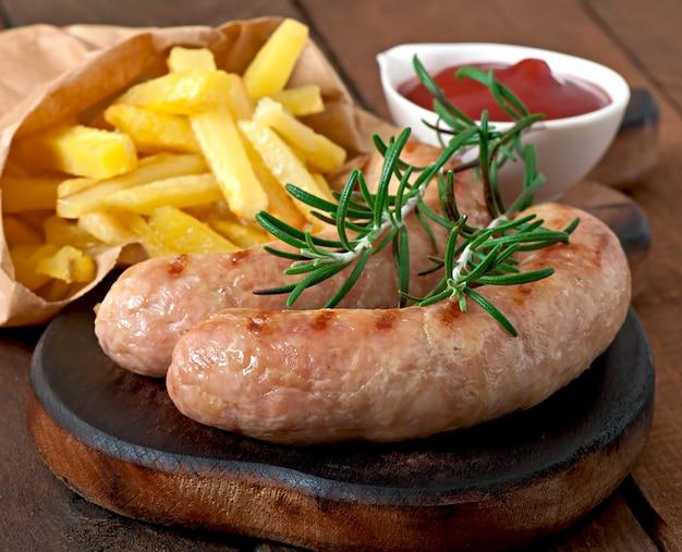 Salsichas de frango grelhadas com um prato de batatas fritas