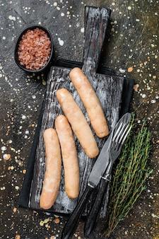 Salsichas de frango grelhado em uma placa de madeira. fundo marrom. vista do topo.