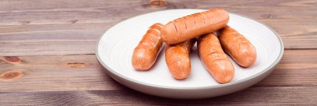 Salsichas de frango grelhado, prontas para comer em um prato sobre uma mesa de madeira