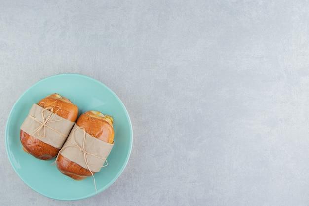 Salsichas de pastelaria deliciosa na placa azul.