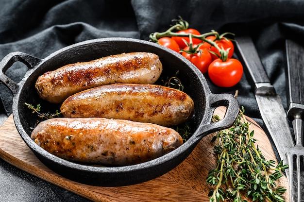Salsichas de porco em uma panela de ferro fundido.