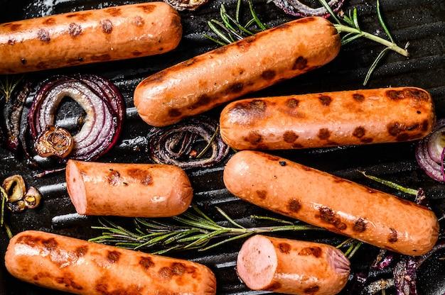 Salsichas de porco grelhadas com cebola, alho e alecrim em uma panela.