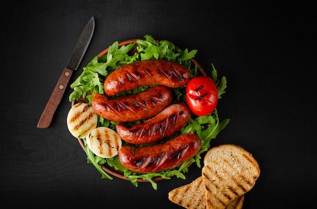 Salsichas de porco grelhadas com rúcula e legumes no preto