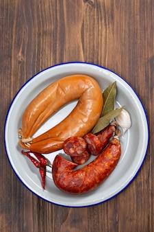 Salsichas defumadas no prato com pimentos