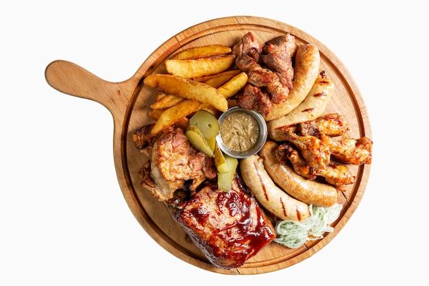 Salsichas defumadas sortidas, carne e batatas fritas com molho em uma placa de madeira. apetitoso lanche de cerveja. vista do topo. isolado sobre o branco