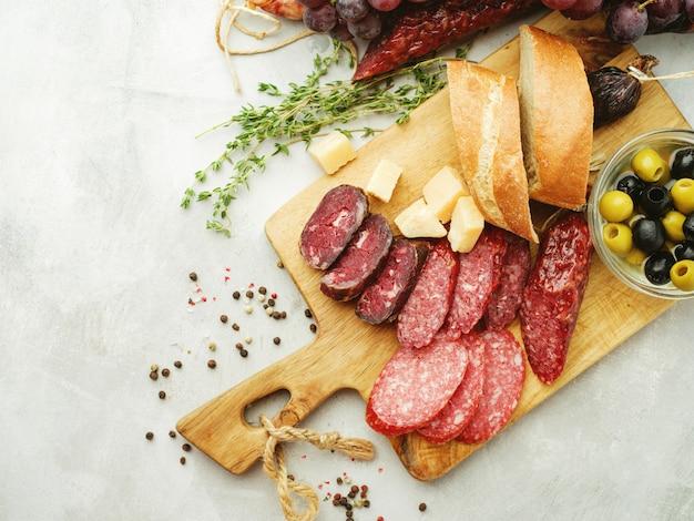 Salsichas diferentes com queijo, uvas e azeitona. salame fatiado em estilo rústico