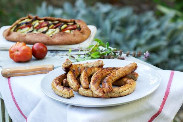 Salsichas e tortas vegetarianas com legumes e ervas em uma mesa de madeira no jardim.