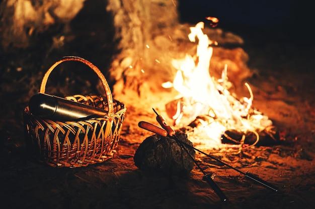 Salsichas em espetos e uma garrafa térmica na cesta contra o fogo à noite.