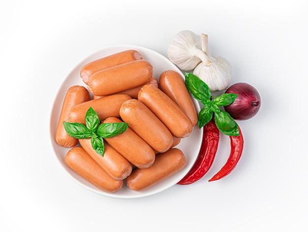 Salsichas em um prato branco, cebola, alho e pimenta isolado em um fundo branco. vista do topo. produtos semi-acabados.