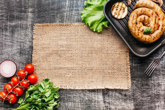 Salsichas espirais grelhadas na panela com vegetais orgânicos sobre fundo cinza de madeira