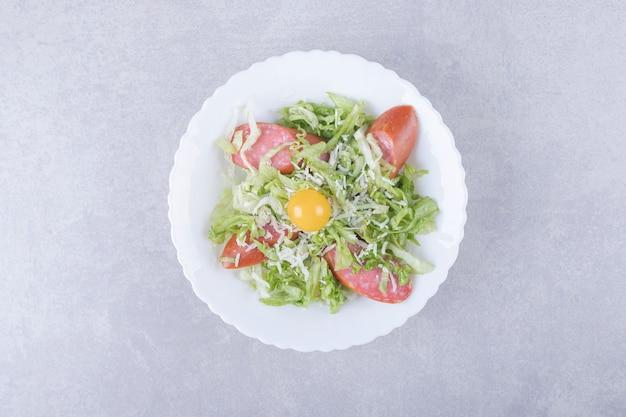 Salsichas fatiadas, alface e gema de ovo em uma tigela branca.