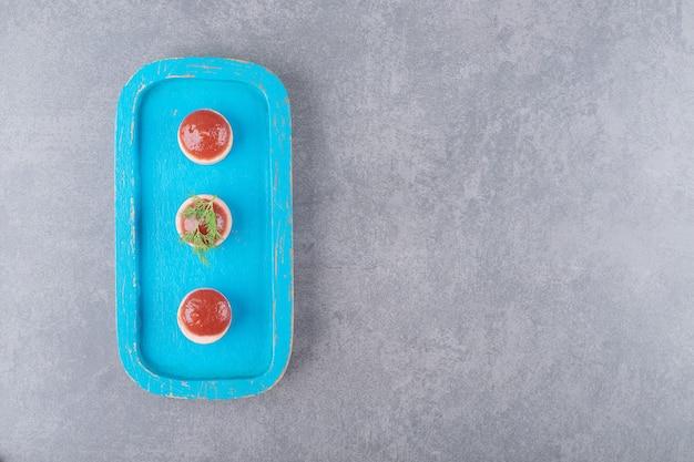 Salsichas fatiadas com ketchup na placa de madeira azul
