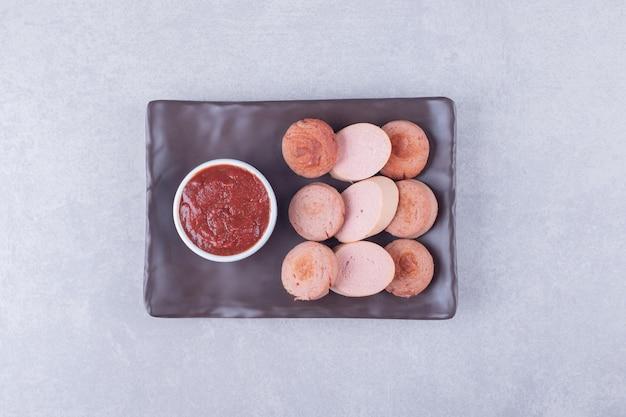 Salsichas fatiadas com ketchup na placa escura.