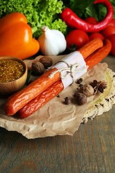 Salsichas finas defumadas, mostarda na tigela e temperos na tábua de cortar