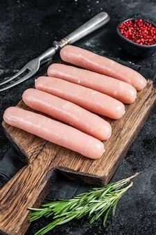 Salsichas frescas de frango cru e carne de peru em uma placa de madeira com alecrim