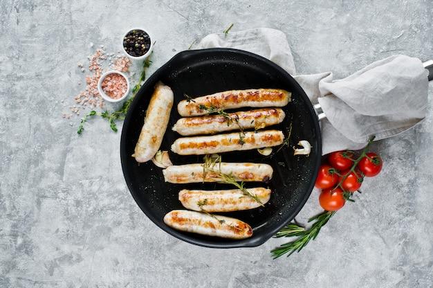 Salsichas fritadas sortidos em uma frigideira, carne de porco, carne, galinha, turquia.