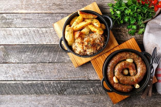 Salsichas fritas caseiras em uma panela com enfeite. estilo rústico. vista do topo