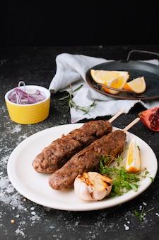 Salsichas fritas com a adição de ervas, legumes, alho, limão e cebola no prato