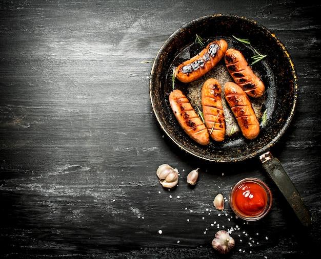 Salsichas fritas com alho e molho de tomate na frigideira. na lousa.