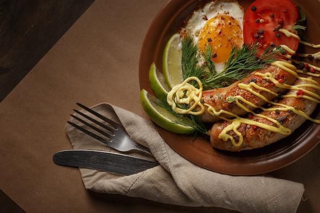 Salsichas fritas com especiarias, legumes e verduras.