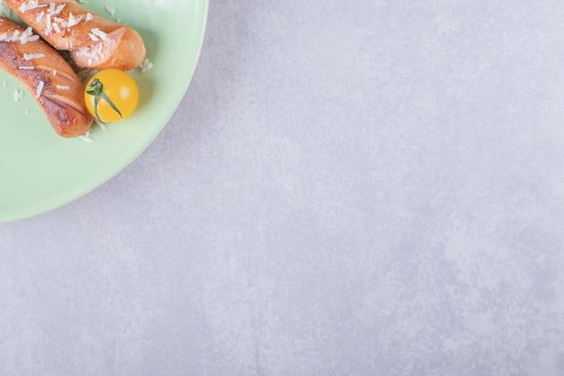 Salsichas fritas deliciosas e tomate cereja na placa verde.