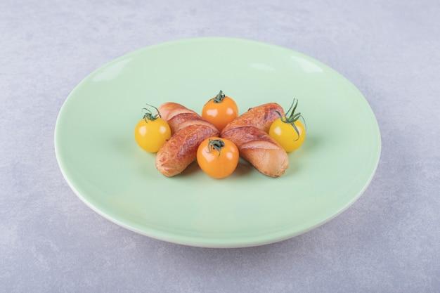 Salsichas fritas e tomate cereja na placa verde.