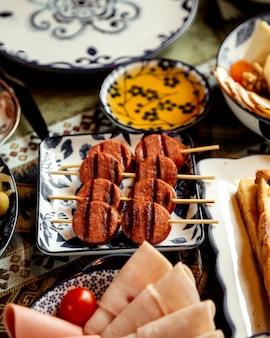 Salsichas fritas fatiadas na vara