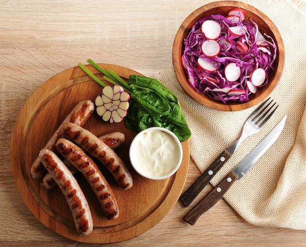 Salsichas fritas na grelha com molho de natas e uma salada de rabanete com repolho roxo