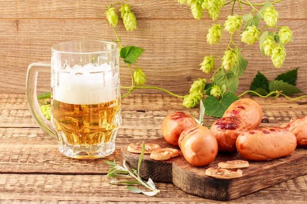 Salsichas fritas na tábua de madeira e copo de cerveja no fundo de madeira com a planta de lúpulo. churrasco, piquenique