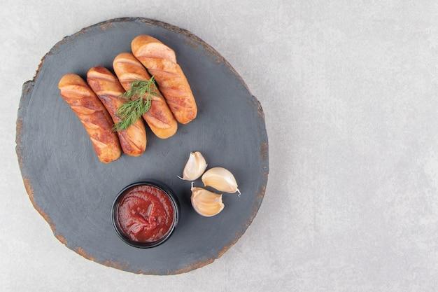 Salsichas fritas saborosas, alho e ketchup na peça de madeira.
