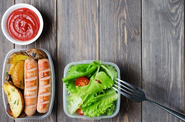 Salsichas grelhadas, batatas, alface verde com tomate em uma caixa de plástico.