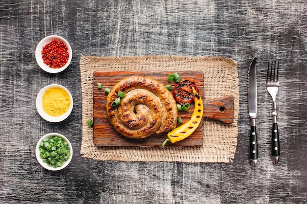 Salsichas grelhadas caseiras em espiral na placa de corte perto de ingrediente saudável dispostos em linha