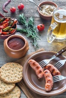 Salsichas grelhadas com aperitivos e caneca de cerveja