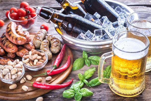Salsichas grelhadas com aperitivos e canecas de cerveja